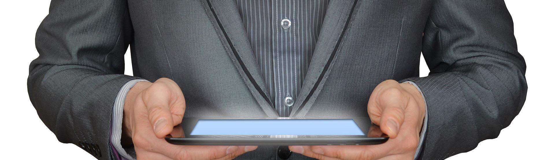 Un empresario en traje tiene una tablet entre sus manos y parece consultar un programa informático con interés.