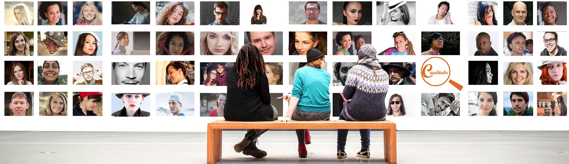Tres jóvenes sentado en un banco y mirando las fotografías de otra gente colgada en una pared blanca.